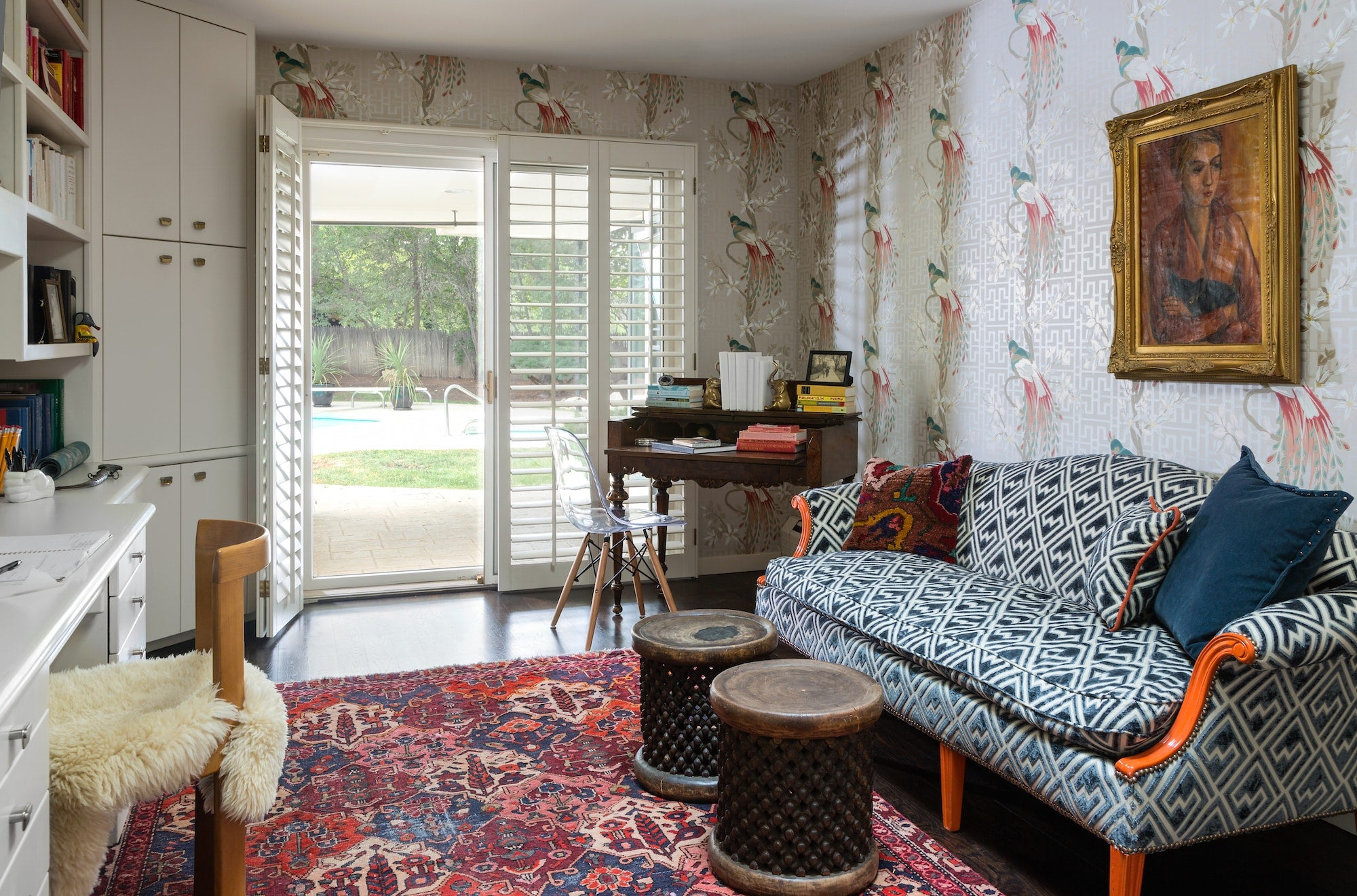 Andrea Schumacher's own study in Bow Mar, Colorado, holds true to her curated-over-time philosophy, filled with pieces and moments that she's collected over the years. Here, she followed her rule of three with Nina Campbell's whimsical Paradiso wallcovering, a modern geometric print on the sofa and a vintage Kurdish rug. Photo by Emily Minton Redfield