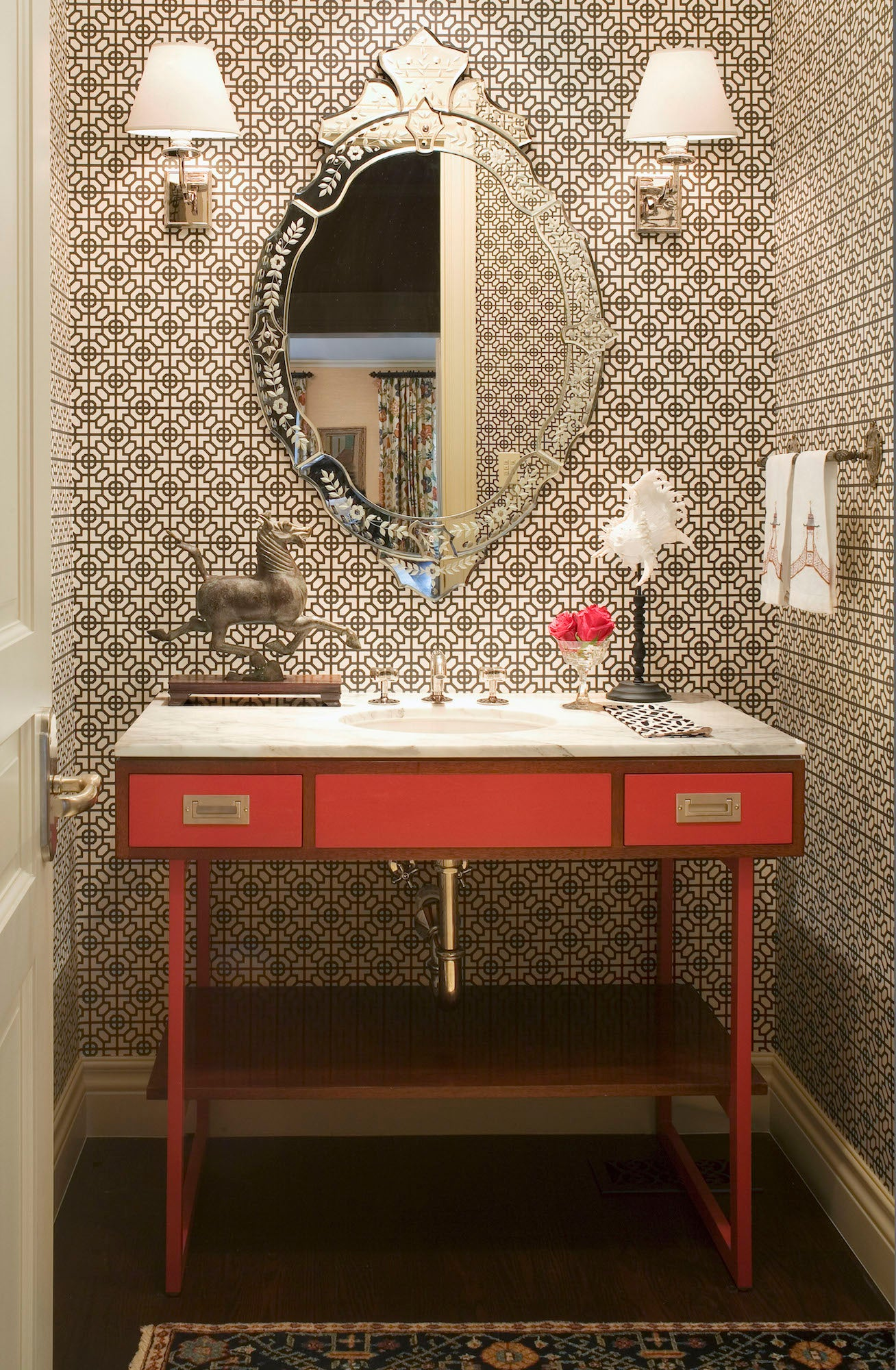Andrea Schumacher transformed a petite powder room into a statement-making space with a vibrant red vanity from Waterworks and Sussex wallpaper in black and white by Designers Guild. Photo by Emily Minton Redfield
