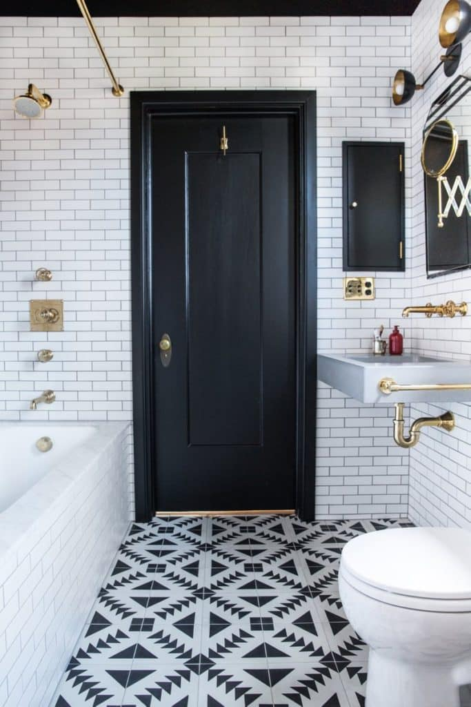 In this Oakland, California, bathroom by Katie Martinez, brass hardware pops against the black and white color scheme.