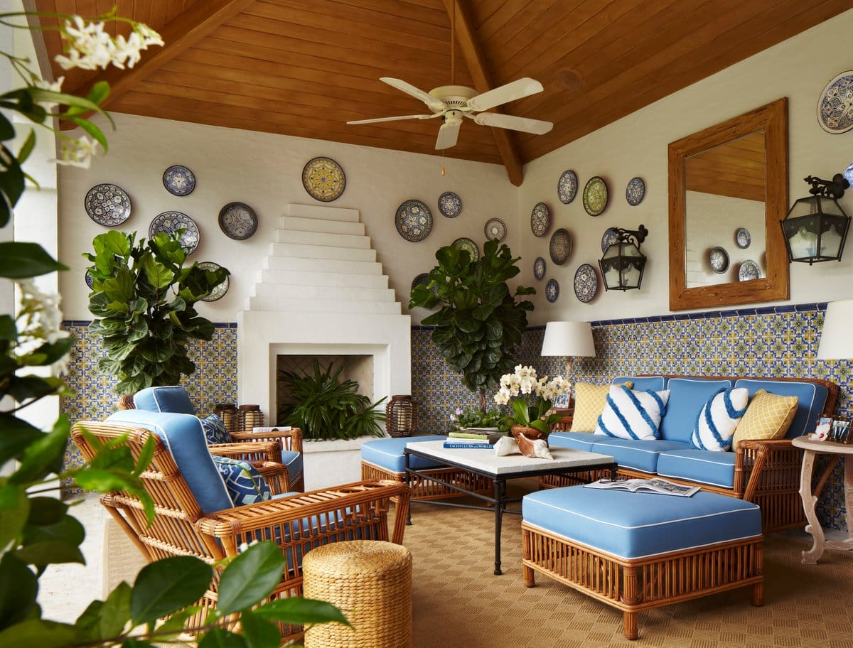 An elegant patio in a Palm Beach residence by Celerie Kemble has comfortable rattan seating.
