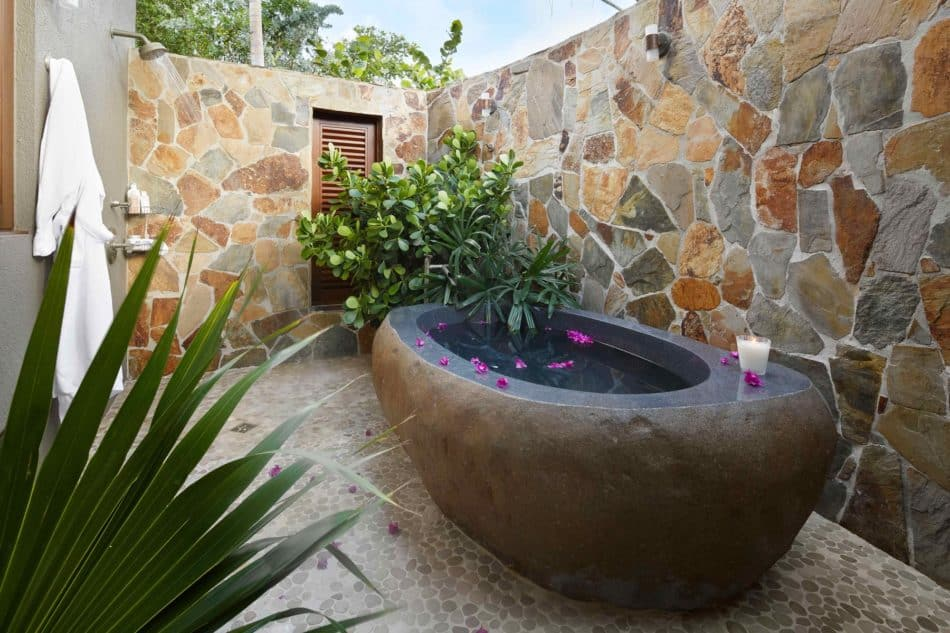 Outdoor stone bathtub and shower by Soucie Horner