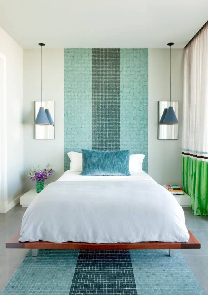 A bedroom in this Frank Roop–designed Miami Beach apartment has swimming pool-style tiles that extend from the floor up to the ceiling.