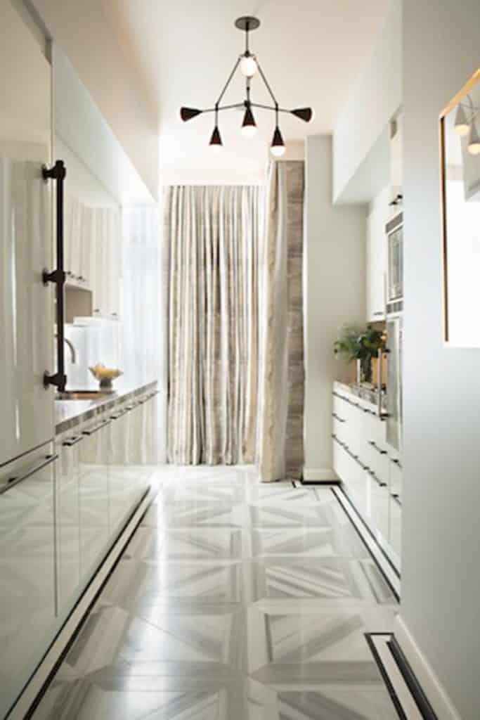 This gray and white floor adds a punch of pattern to this otherwise monochrome kitchen by Woodson & Rummerfield