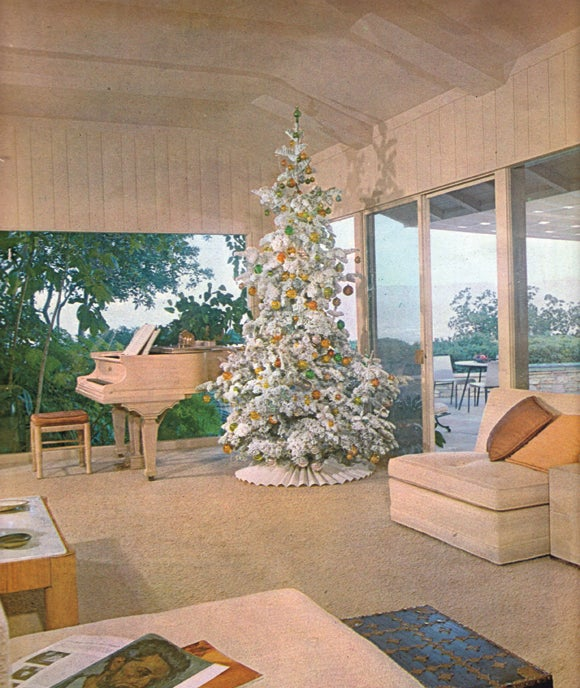 a christmas tree covered in faux snow brings a festive flair to a mid century modern living room published in the december 1961 issue of house beautiful