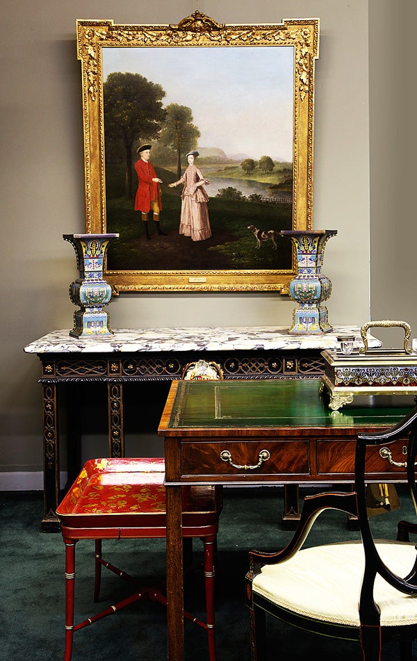 A portrait by 18th-century English painter Arthur Devis hangs over a George II ebonized-and-gilt-marble-top console table that commemorates the marriage of Thomas Pelham to Anne Frankland in 1754 and bears the arms of both families; in the foreground is a Regency writing table in mahogany, ca. 1785, and a Victorian gilt papier-mâché tray, ca. 1850.