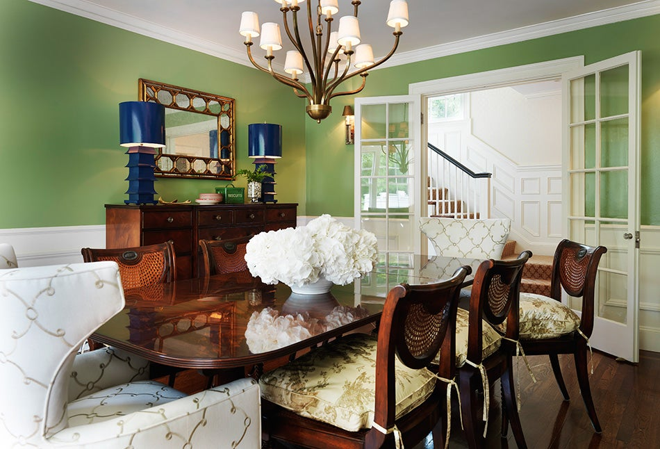 Tradition meets the unexpected in the dining room of a Wellesley, Massachusetts, home, where the Kravat fabric on the wingchairs, the multi-armed chandelier and the pair of porcelain pagoda lamps add a dose of whimsy. Photo by Nat Rea