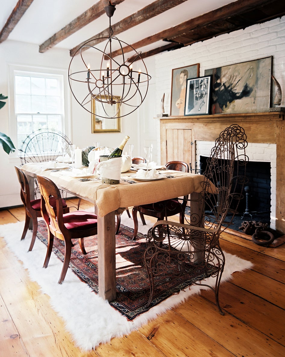 In the dining room of the Sag Harbor house, vintage Regency dining chairs are paired with sculptural metal chairs from Mexico. Photo by Patrick Cline, courtesy of Lonny