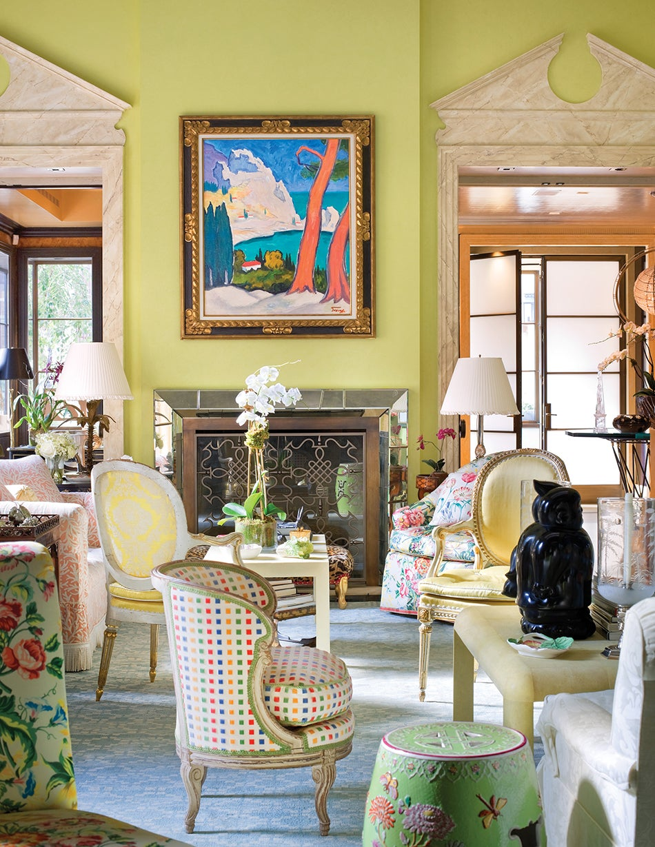 Mario Buatta increased the grandeur of the already-impressive  living room of Hilary and Wilbur Ross's Manhattan pied-à-terre by adding overdoor pediments and dentil molding. Photo by Scott Frances/Architectural Digest © Condé Nast Publications. Above: The designer stands in front of a whimsical painting that recalls one of his rooms. Photo by Jason Schmidt/Nest