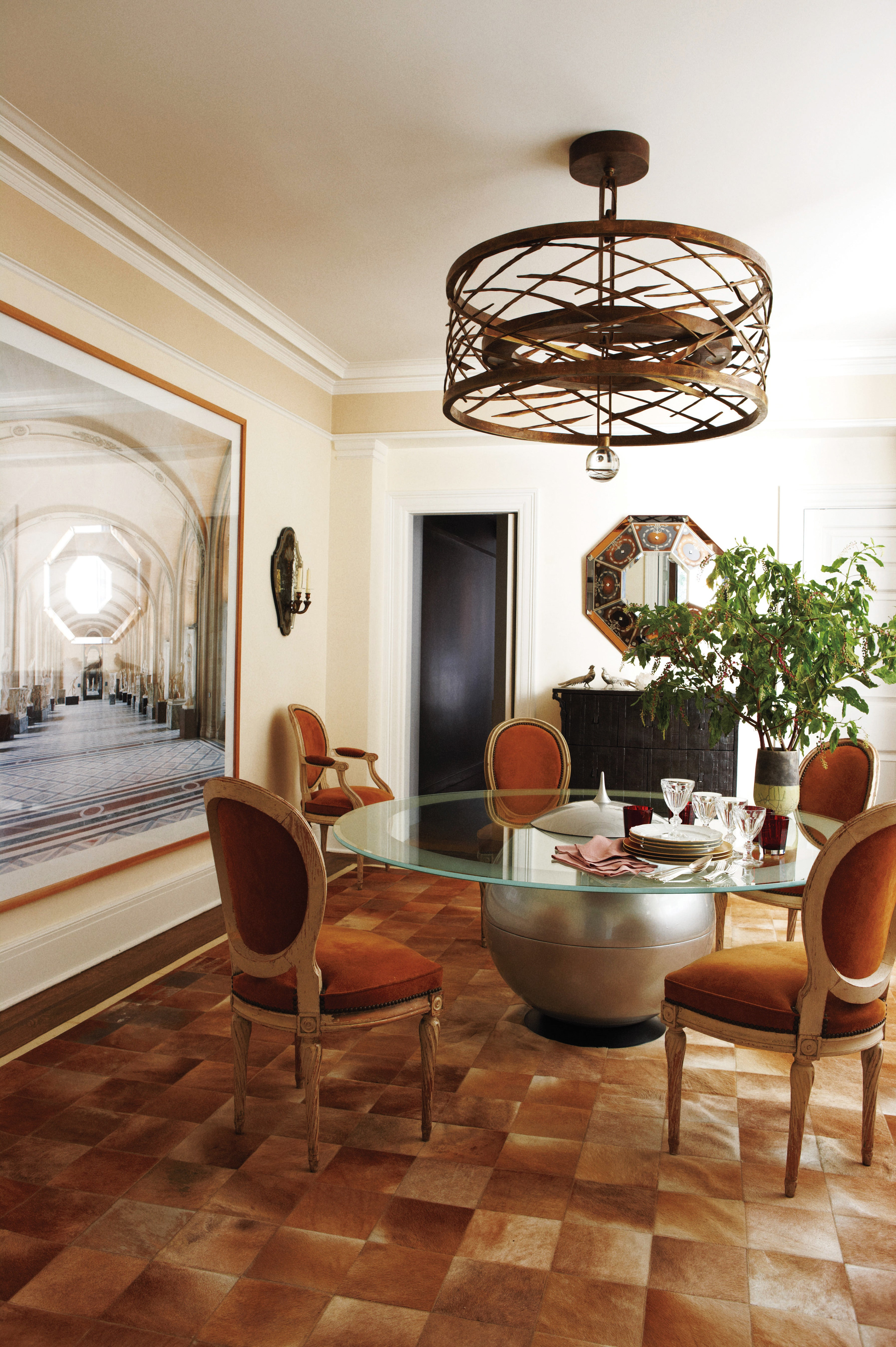 In the Upper East Side apartment, an Hervé Van der Straeten chandelier hangs above a 1980s Italian table, which is encircled by Maison Jansen chairs.