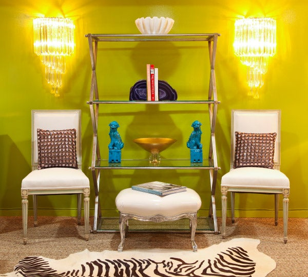 A symmetrical setting at the store includes a metal étagère (ca. 1970) and two painted Louis XVI–style dining chairs (ca. 1950s) with a pair of six-tier Venini crystal sconces (ca. 1960) hanging over them.