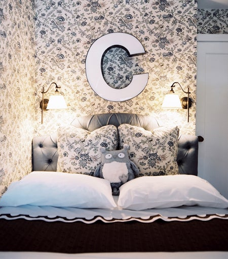 "In a young girl's room, a traditional floral-print Cowtan & Tout fabric does double-duty on the walls and pillows. The designers found the ""C"" at a local vintage shop, and the Scallop bedding is by Matouk. Photo by Patrick Cline"