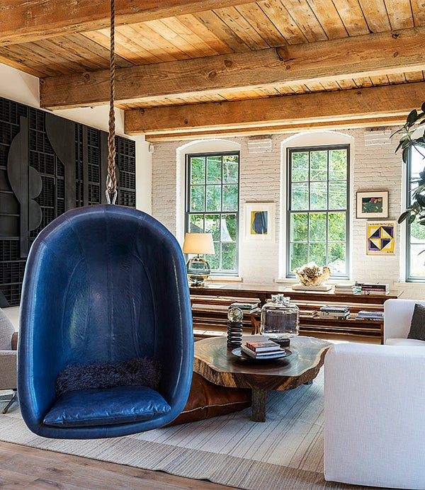 In Huniford's living room, a blue leather chair is suspended from the ceiling and a black wood Louise Nevelson sculpture hangs on the wall on left. Photo by Paul Domzal, Edge Media