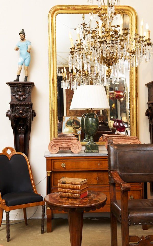 A pair of South American figures flank a Russian chandelier and a French Louis Philippe gilt-wood mirror, all from the 19th century.