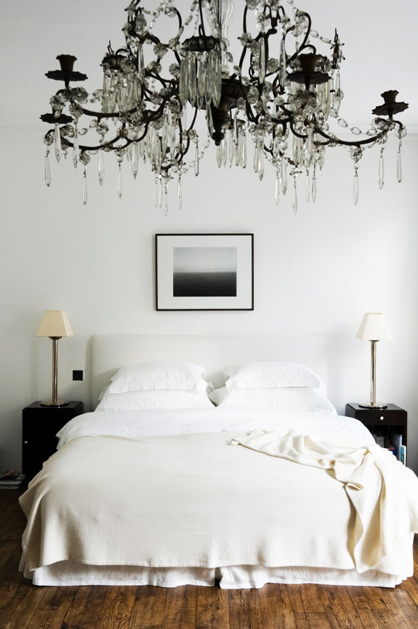 A grand chandelier adds glamour to the otherwise understated bedroom of a London house.
