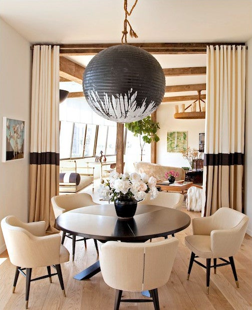 In the dining room of celebrity hairdresser Chris McMillan, the interior designer Trip Haenisch hung a custom black-splattered Noguchi lamp over a table surrounded by Edward Wormley chairs. Photo by Tim Street-Porter