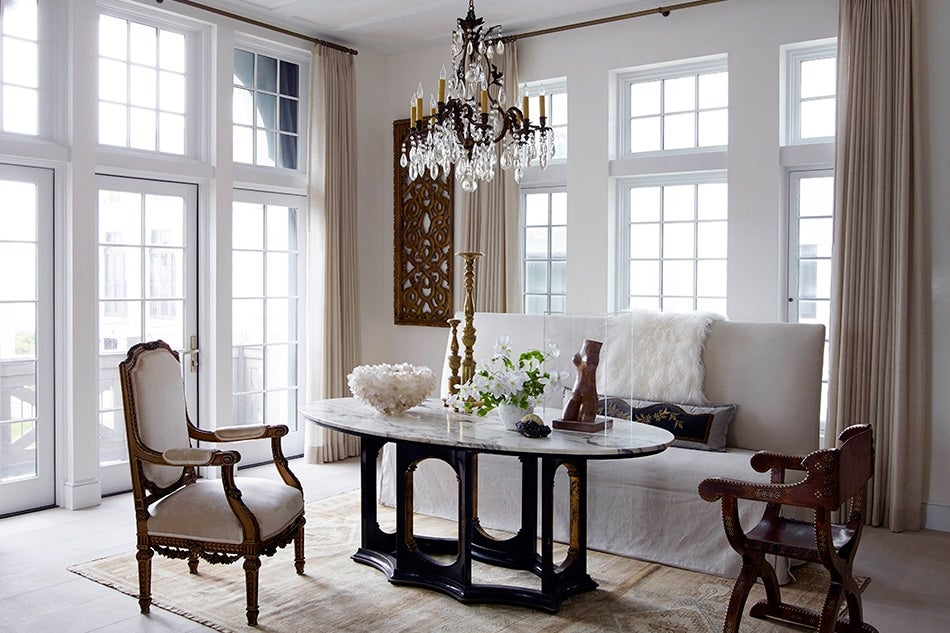 Sitting and dining area with antiques in Alys Beach Florida by Texas architect Michael Imber