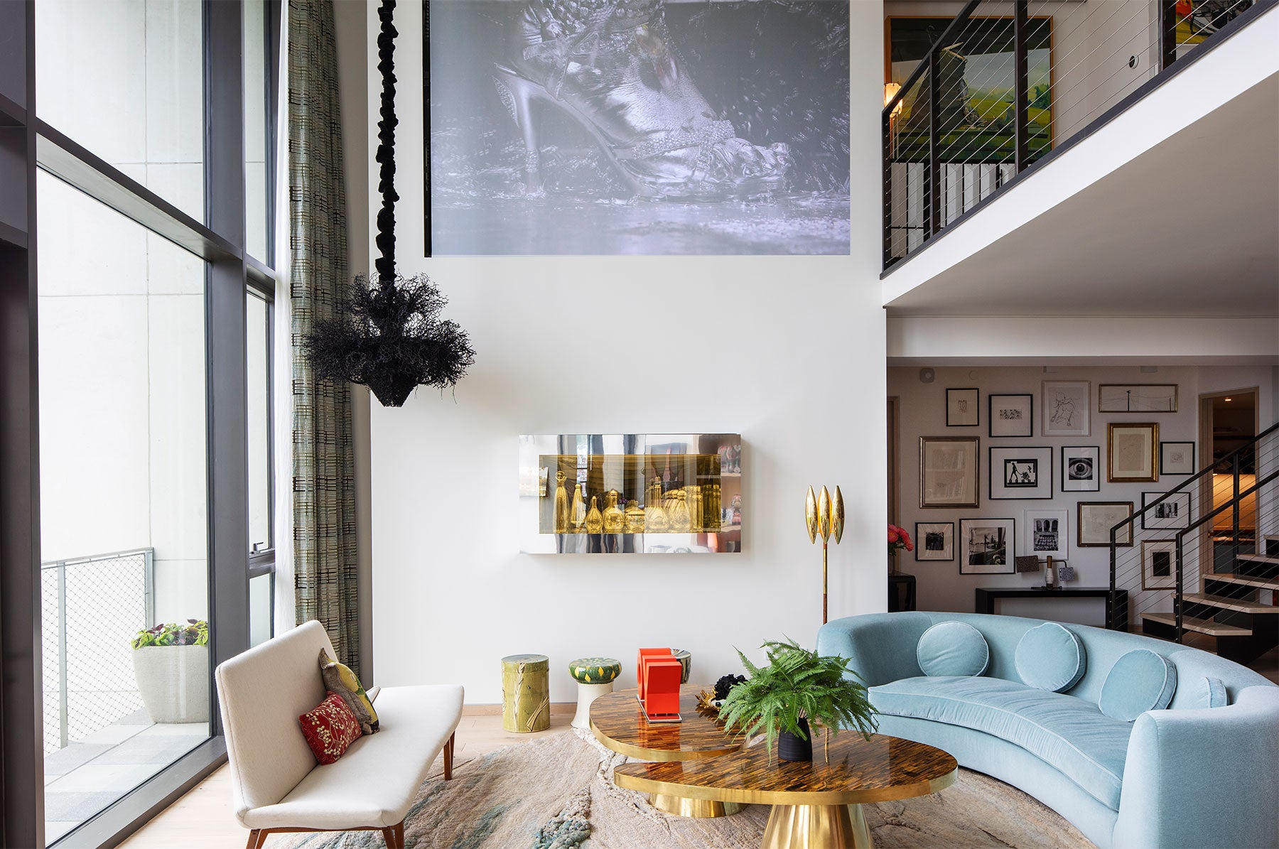 Marilyn Minter video installation is projected on the wall of the living room above a Josiah McEleheny vitrine and 1940s ceramic stools from 1stdibs. The black hanging sculpture is by Petah Clyne, and the sofa is by India Mahdavi