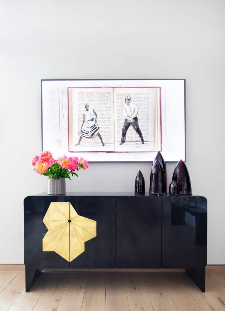 William Kentridge artwork is mounted above a Gloria Cortina cabinet and ceramics from Cristina Grajales Gallery