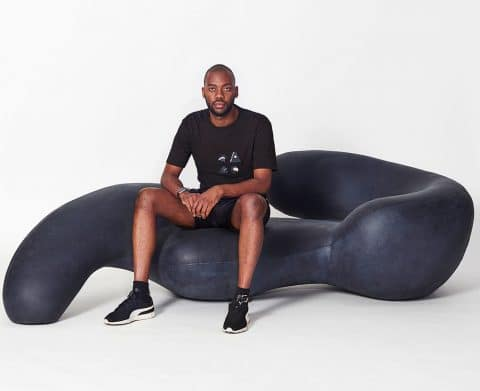 Rich Mnisi, designer, sits on a chaise of his own design